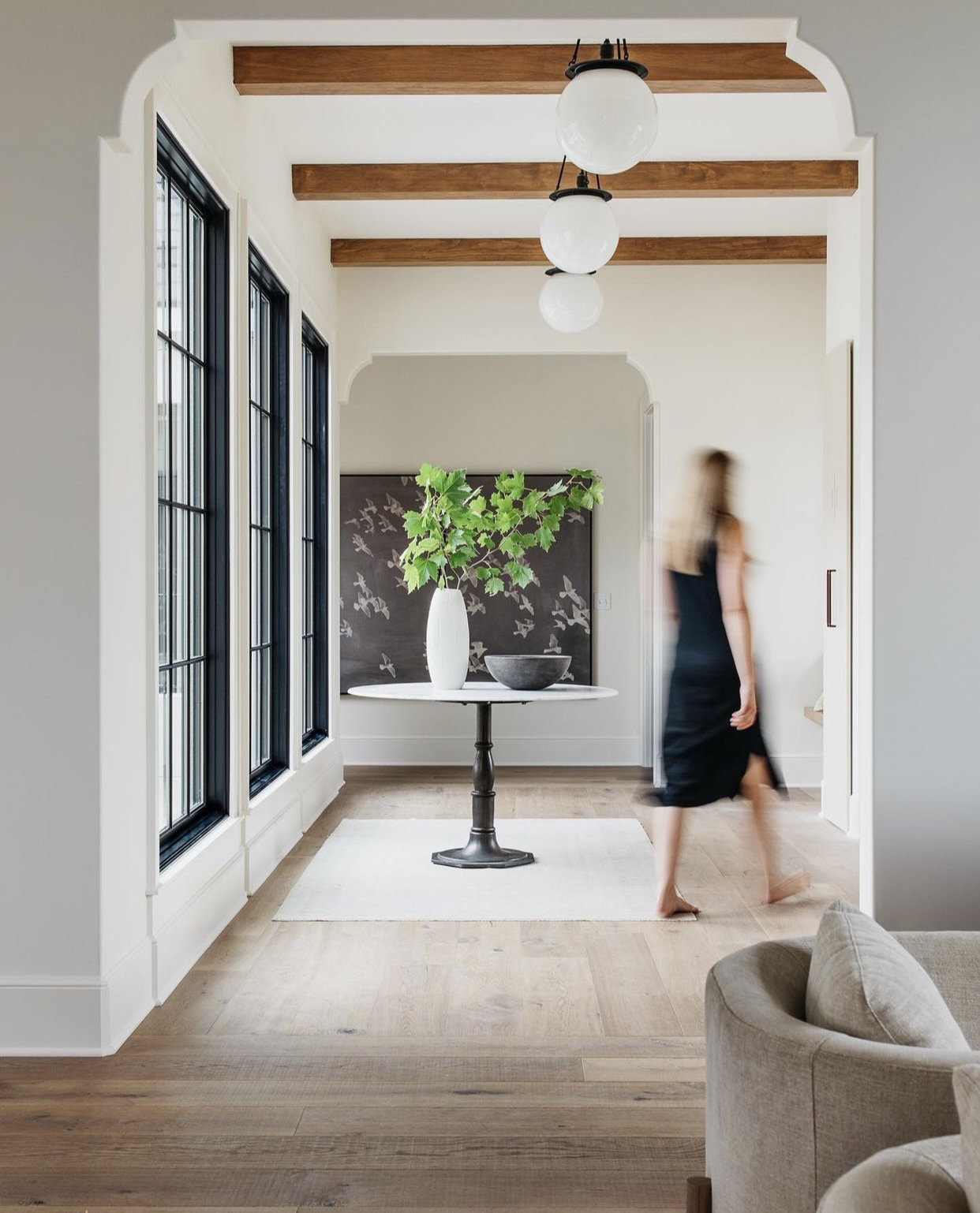 Elegant entry with white marble table, and round white glass pendants. Light wood floors soften the space.