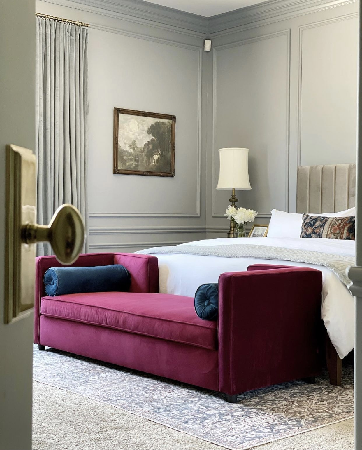 Traditional bedroom with blue gray walls, picture frame molding and a bright sofa.