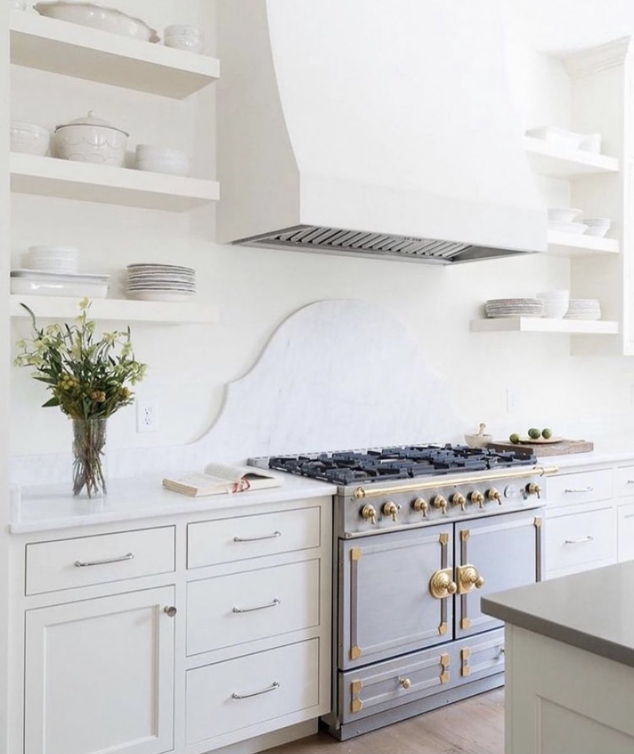 Traditional white kitchen with marble counters intricate details and a modern white plaster hood.