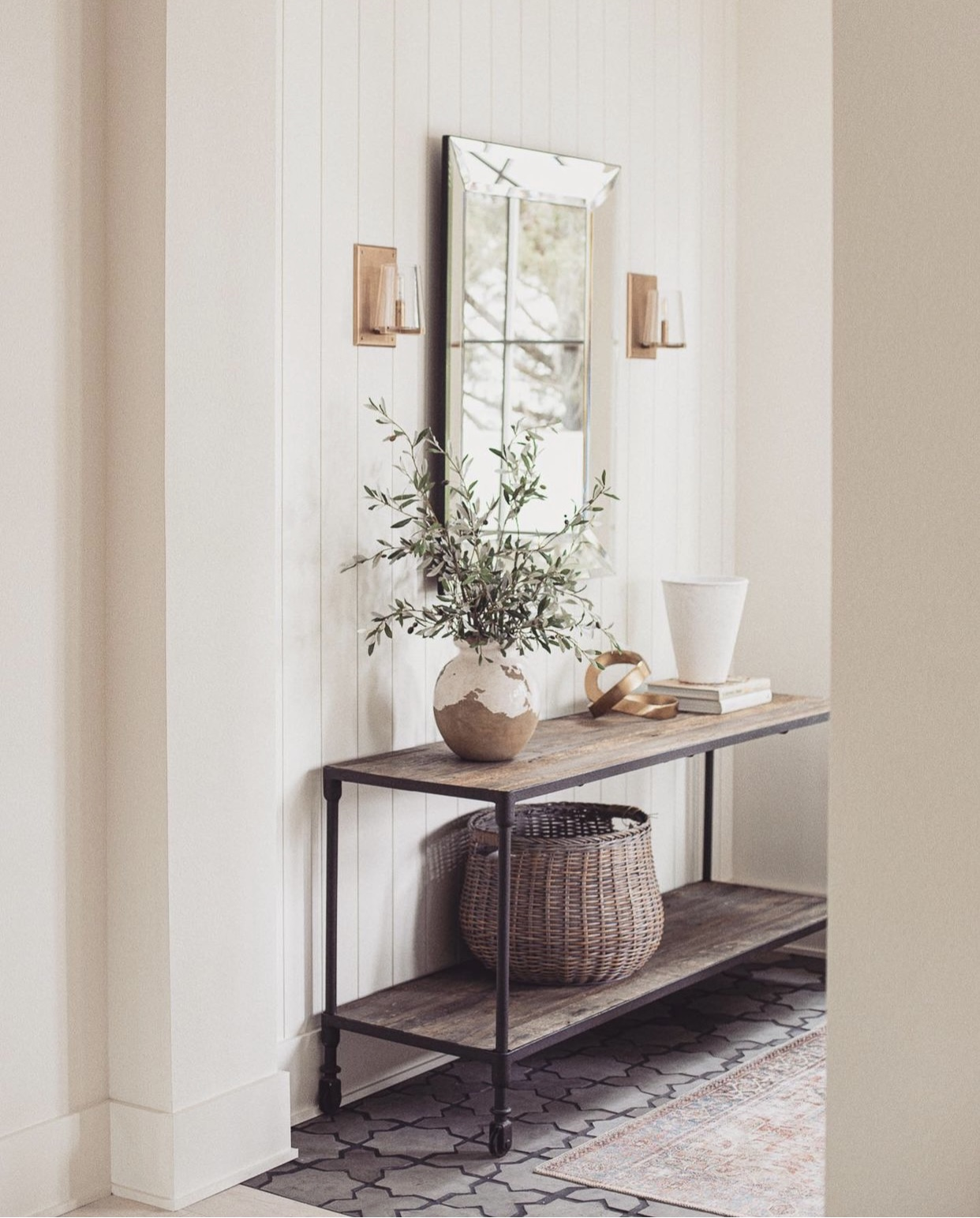 Soft neutral colored entry with wood and steel table, earthy accessories, terra-cotta patterned floors, and white vertical shiplap.