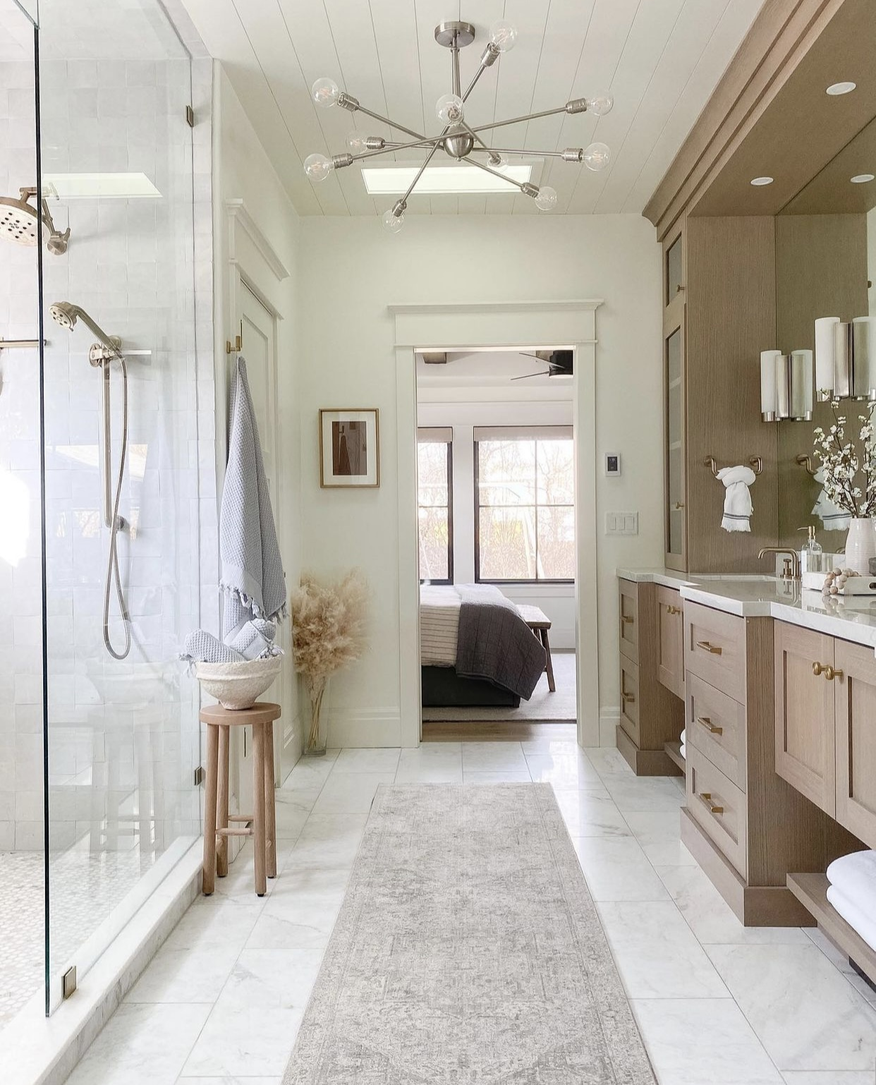 White marble bathroom in soft neutral colors with vintage inspired runner and light wood cabinetry.